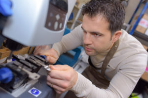 Locksmith using a key cutting machine to duplicate a key for a customer