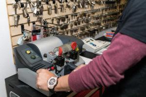 Locksmith cutting a key in store for a customer on their key cutting machine